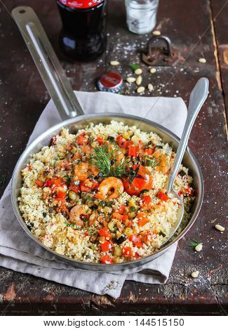 Homemade couscous with shrimps, eggplant, zucchini, red pepper, cherry tomatoes, pine nuts and fresh dill in a pan ready for lunch or dinner on a wooden table, selective focus