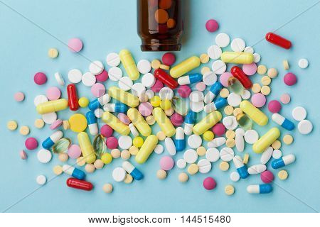 Colorful drug pills on blue background, pharmaceutical and medical concept.
