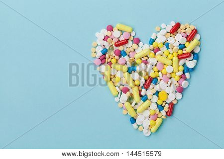 Colorful drug pills in shape of heart on blue background. Pharmaceutical and medical concept.