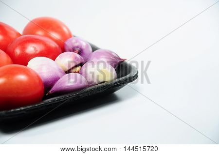 Fresh purple organic shallots and red tomatoes on black tray