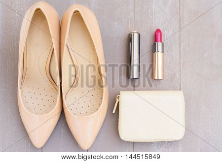 Nude colored high heels still life with wallet and red lipstick, top view