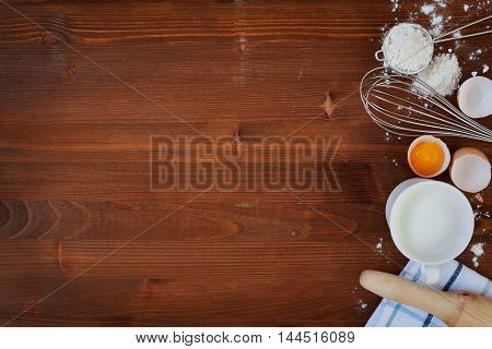 Ingredients for baking dough including flour, eggs, milk, whisk and rolling pin on wooden rustic background. Empty space for text. Top view.