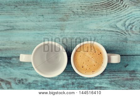 Empty and full cup of fresh coffee on vintage wooden blue table.