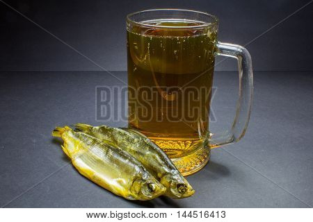Beer And Dried Fish Snack On Black Background.