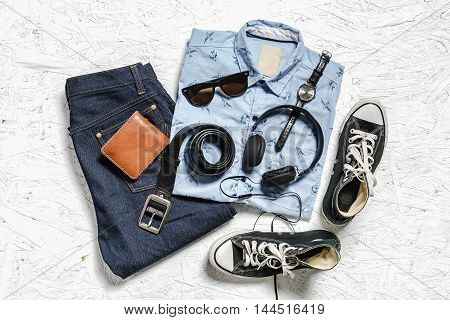 Overhead view of men's casual outfits on white wooden board Essential items of traveler