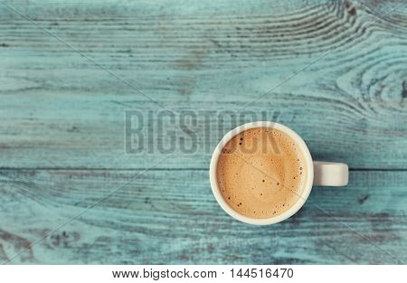 Cup of fresh coffee on vintage wooden blue table.