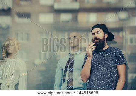 Bearded Man Smoking Near Showcase
