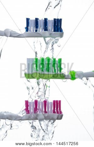 Three tooth brushes under splashing water backlit isolated on white background.