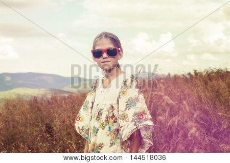 Teen blonde in hippie style posing on a mountain meadow. Bright red sunglasses. Vintage. Toned image