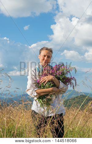 Young woman holds a big bouquet of wildflowers and looking at the camera. Summer cloudy day on a mountain meadow. Carpathian mountains