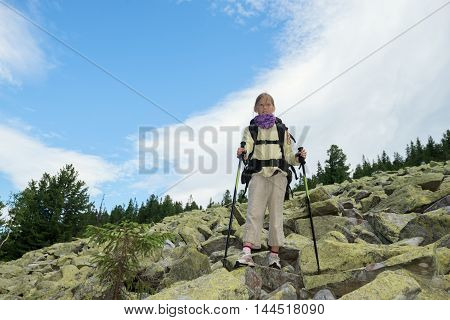 Cool hiker girl standing on a moraine and looks into the distance. Ukrainian Carpathians Gorgan