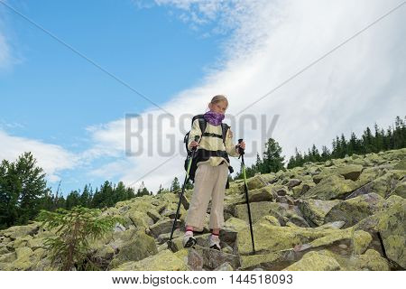 Cool hiker girl standing on a moraine and looking at the camera. Trekking in the Ukrainian Carpathians