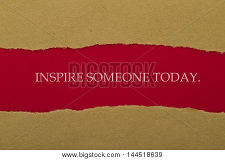 INSPIRE SOMEONE TODAY written under torn paper.