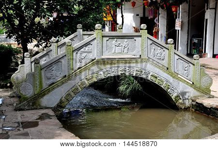 Ping Le China - September 28 2010: A traditional Chinese bridge with carved bas relief panels graces a small stream running through the center of the town's principal street