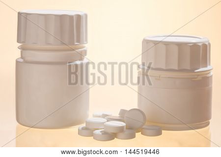 Pill bottles and round white tablets. Closeup