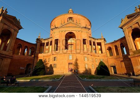Bologna Italy - August 25 2016: Tourists at sunset in front of the facade of the Catholic Cathedral of St. Luke on a hillside of Bologna Italy.
