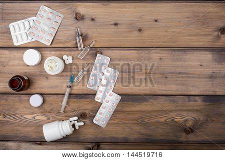 Setup from various pill bottles an blister pack on wooden table