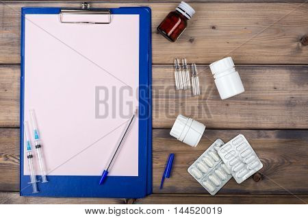 Blank page and various drug packaging on wooden background