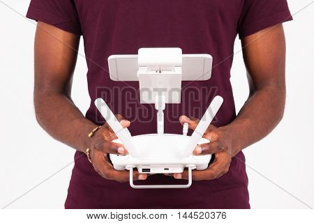 African American Young Man Holding A Drone Remote Control Over White Background