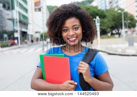 Laughing female student from Africa in blue shirt looking at camera in city