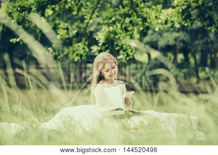 small girl kid with long blonde hair and pretty smiling happy face in prom princess white dress standing sunny day outdoor on natural background with fruit basket of red apples peach and cherry and book