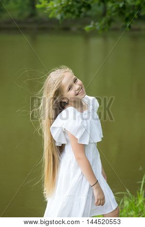 small girl kid with long blonde hair and pretty smiling happy face in prom princess white dress standing sunny day outdoor near water