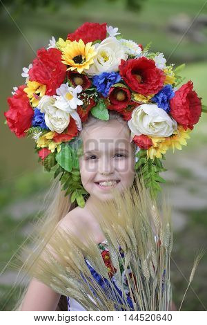 small girl kid with long blonde hair and pretty happy smiling face in prom embriodered white dress and colorful flower national ukrainian wreath crown on head outdoor with spikelet grass