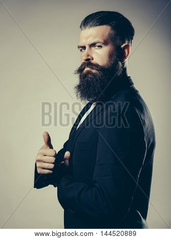 Handsome young man with long beard and moustache in black jacket with super gesture in studio on grey background