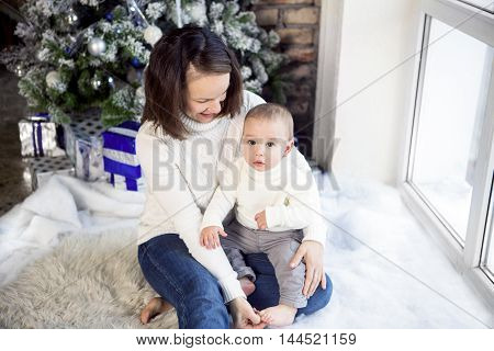 Happy mother with her baby boy siting near the Christmas tree