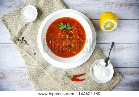 Red soup with sour cream and parsley on the table