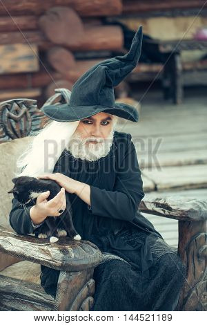 Old man in wizard costume hat for Halloween strokes black cat and sits in wooden chair on log house background