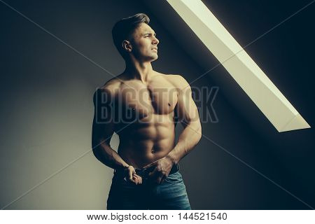 Sexy young man with muscular body and bare torso posing near window