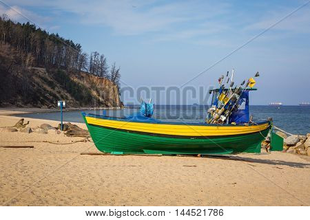 Baltic beach with fishing boat at Orlowo cliff, Poland