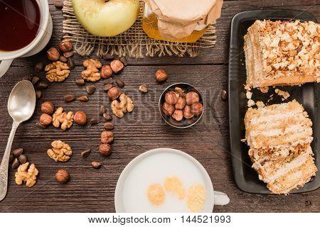 Homemade nut cake with chocolate cream, various nuts, tea and milk on dark wood surface