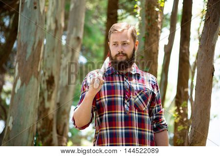 Portrait of an attractive young lumberjack who walks through the woods in search of the tree