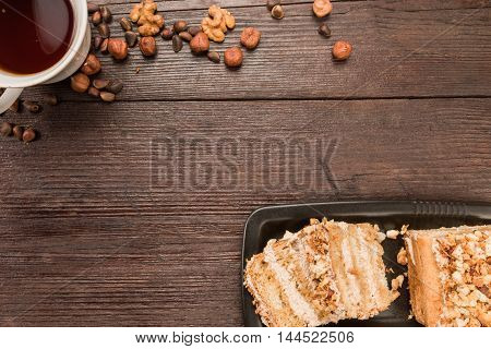 Homemade nut cake with chocolate cream, various nuts and cup of tea on dark wood surface