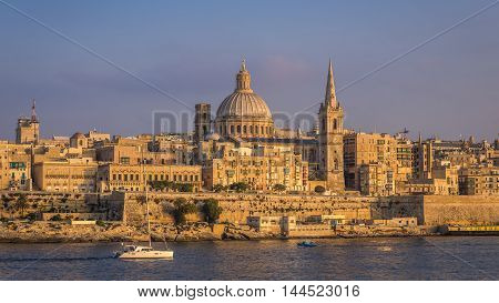 Valletta Malta - Sailboat and the famous St.Paul's Cathedral with the ancient city of Valletta at sunset