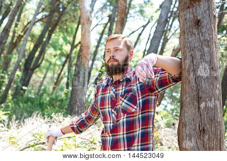 Portrait of an attractive young lumberjack who is leaning against a tree