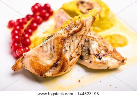 Roasted chicken breast stuffed with champignon mushrooms served with vegetable puree and red currant isolated on white background, selective focus
