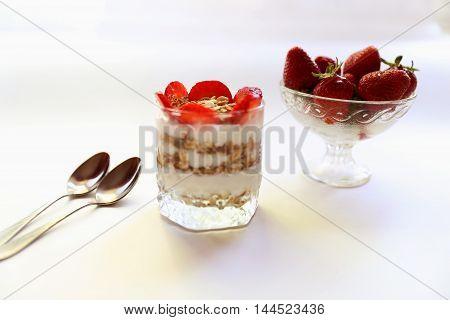 Strawberry yogurt with granola and slices of strawberry