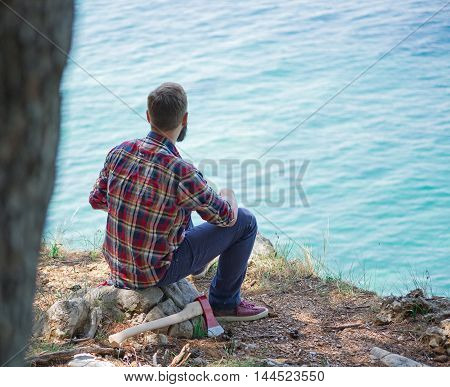 Portrait of an attractive young lumberjack who is resting after cutting a tree