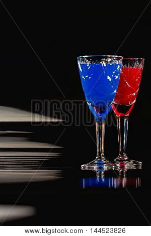 Wineglasses of cut-glass full of colorful liquids over black reflective background