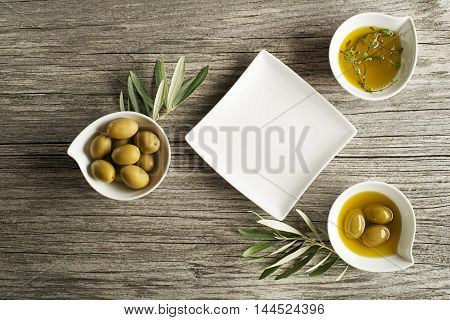 Olive oil with fresh herbs and plate on wooden background.
