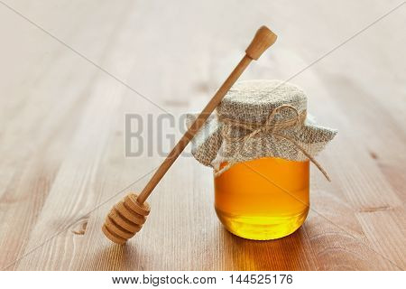 Honey in a pot or jar with twine tied in a bow and dipper on a wooden background.