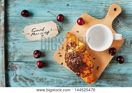 Tasty breakfast with fresh croissant, empty cup of coffee, cherries and notes good morning on a wooden table.