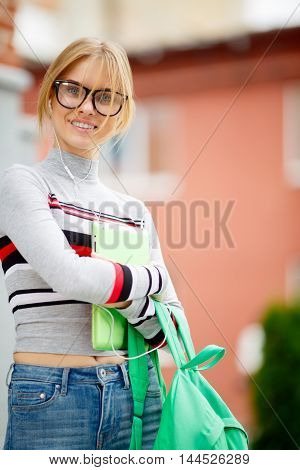blonde spectacled holding tablet and Backpack on street