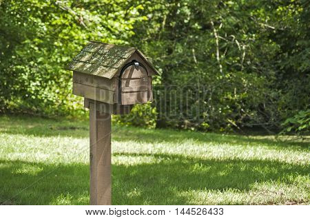 American outdoor wooden mailbox on wooden support