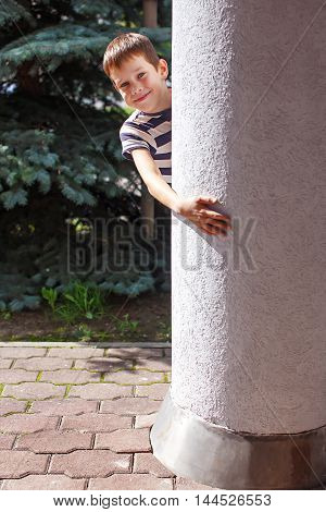 smiling boy hiding behind a pillar. play bo-peep. child playing hide and seek outdoors peeking from behind a pillar
