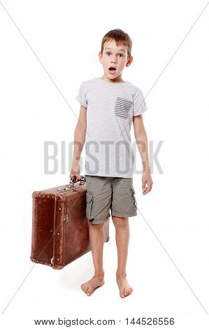 surprised boy with suitcase in hand isolated in white background. barefoot child opened his mouth in surprise. concept of traveling people