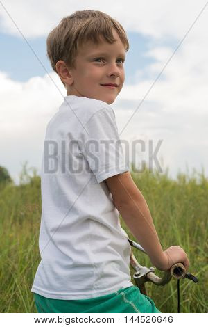 Boy Riding A Bike Outdoors On A Sunny Day